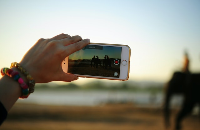 A person holding a mobile filming and recording a scene