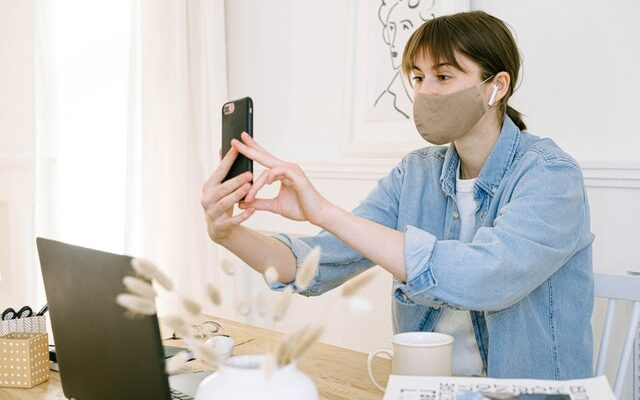 Lady wears a face mask and holds her mobile phone to her face