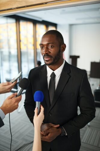 A man in a suit prepares to give media interviews