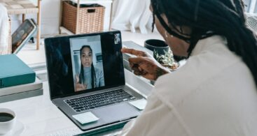 A woman on a laptop talks to another woman via videocall