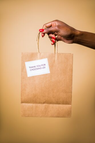 A hand holds a paper bag with a thank you note